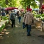 Menschen auf dem Wochenmarkt mit Obst- und Gemüseständen
