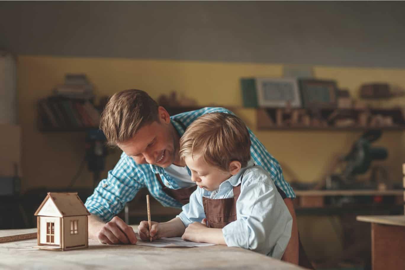 Vater und Sohn entwerfen in der Werkstatt gemeinsam ein Haus -Architekt Titelbild