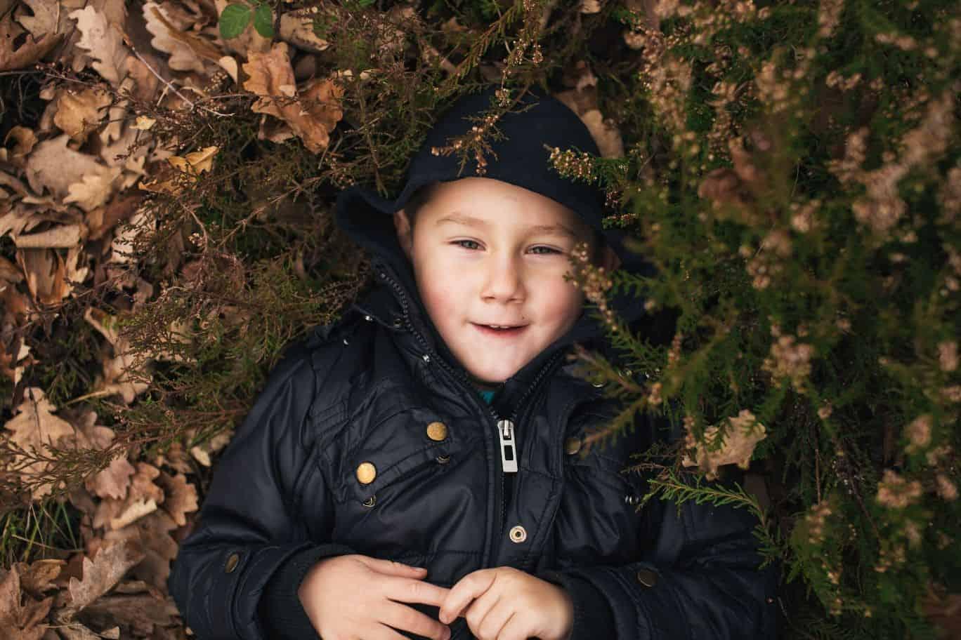 Junge zwischen Blättern am Waldboden - Titelbild zum Slam-Text über Heimat
